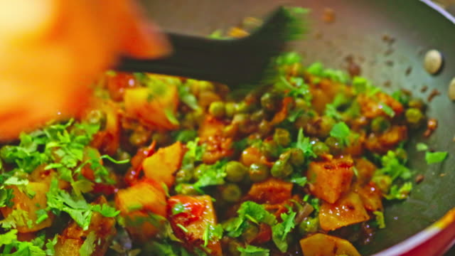 stirring the potato curry after adding fresh cilantro - vegetarian food stock videos & royalty-free footage
