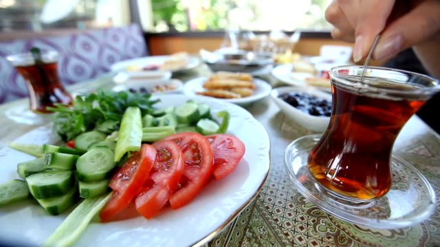 stirring Turkish tea at Turkish breakfast