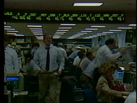 vidéos et rushes de stock brokers busy at work in 1987. - trader