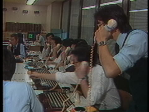 stock brokers talk on telephones in a busy brokerage in japan. - business or economy or employment and labor or financial market or finance or agriculture点の映像素材/bロール