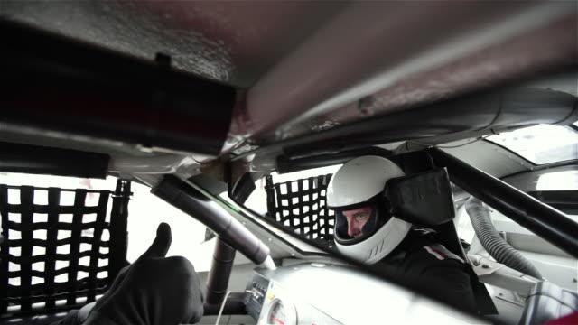 ecu. stock car driver in white helmet keeps eyes focused on the race ahead. - halle gebäude stock-videos und b-roll-filmmaterial