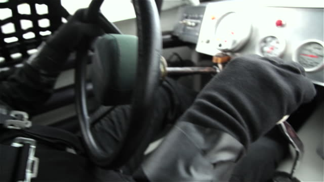 CU. Stock car driver shifts gears with gloved hands.