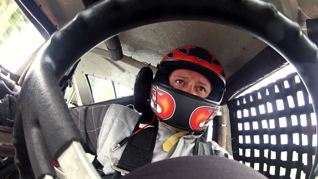 stock car driver turns steering wheel full rotation. (steering wheel pov) - fähigkeit stock-videos und b-roll-filmmaterial