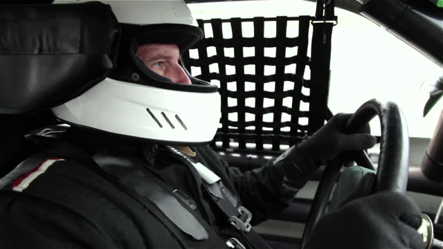 ecu. stock car driver's eyes check rear view mirror and look ahead in the heat of the race. - sports glove stock videos and b-roll footage