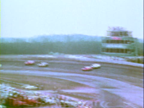 Stock car losing control on bowled turn spinning out and coming to stop near guardrail / 1970 Plymouth Road Runner Superbird racing 1969 Ford Torino...