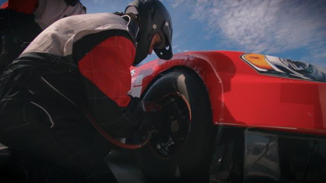 Stock car pit-crewman removes race-car lug-nuts