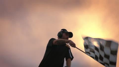 vídeos y material grabado en eventos de stock de slo mo. stock car race official waves checkered flag at golden hour. - línea de meta