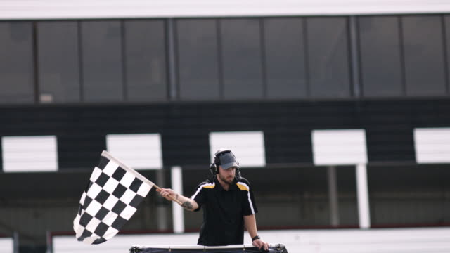 stock car race official waves checkered flag set against dramatic sky. - winning the first prize stock videos and b-roll footage