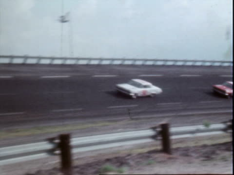 vídeos de stock e filmes b-roll de stock cars on bowled speedway, charlotte world 600 / stock cars 41 0 87 22 4 4 86 / stock cars competing, racing / two male paramedics standing... - 1964