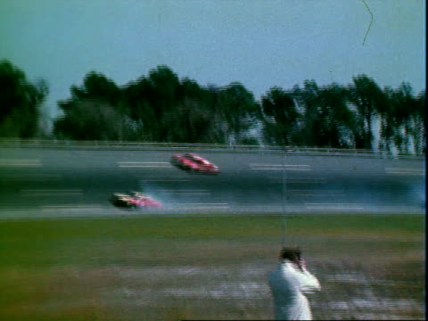 nascar stock cars racing along bowled turn photographers kneeling in infield of daytona international speedway / stock car spinning out after... - circuito di daytona video stock e b–roll
