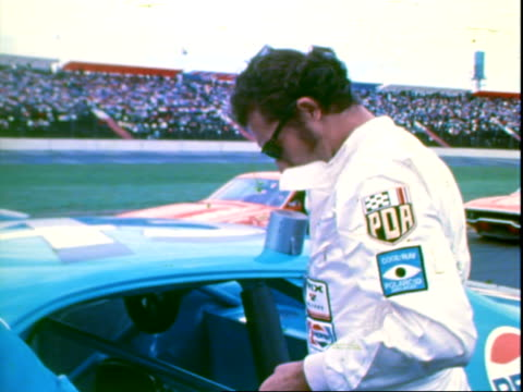 vídeos de stock, filmes e b-roll de stock cars racing coming off bowled turn competing in national 500 stock car race at charlotte motor speedway / professional race car driver richard... - protetor de ouvido