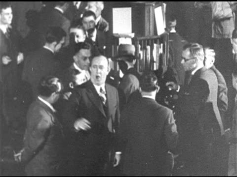 stockvideo's en b-roll-footage met stock exchange floor people gathered w/ male in group shouting ws crowded floor variety headline 'wall st lays an egg' ms td ticker tape from machine... - 1920 1929