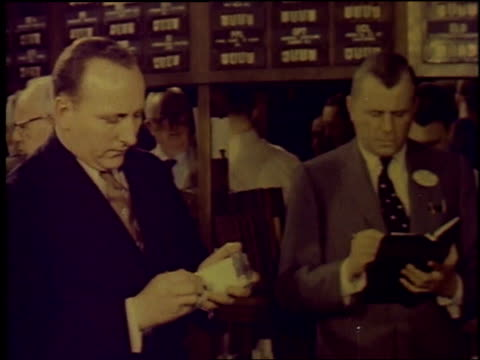 1957 montage stock exchange trading floor, traders talking and writing on notepads, talking on telephone / new york city, new york, united states - new york stock exchange stock videos & royalty-free footage