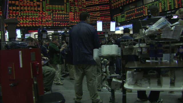 stock market boards surround traders on a stock exchange floor in chicago. - market trader stock videos & royalty-free footage