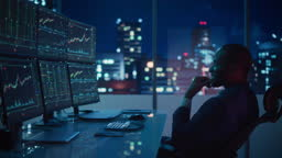 Stock Market Day Trader Working on Computer with Multi-Monitor Workstation with Real-Time Investmentment Charts. Successful African American Businessman Punches Air for Winning a Trade.