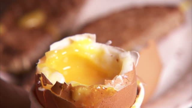 stock shots of boiled eggs and soldiers or eggy soldiers with shots of eggs being cracked with knife and toast being dipped into runny egg yolk - egg yolk stock videos and b-roll footage