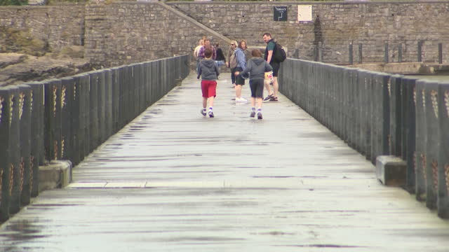 stock shots of people walking by seaside on cloudy murky day in westonsupermare on on 31st july 2017 - weston super mare stock videos and b-roll footage