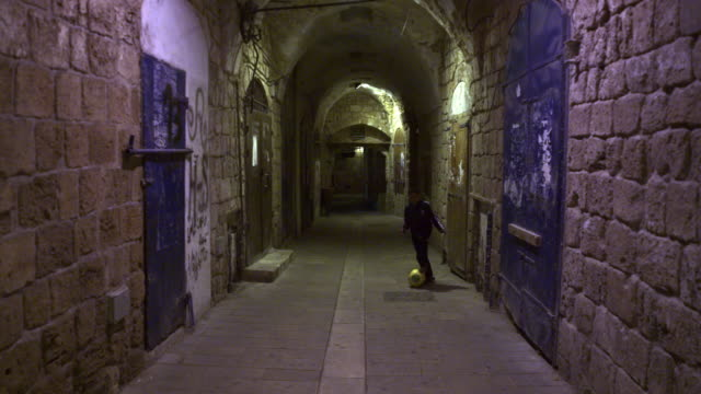 stock video footage of a boy controlling a soccer ball in an alley filmed in israel at 4k with red. - akko stock videos and b-roll footage
