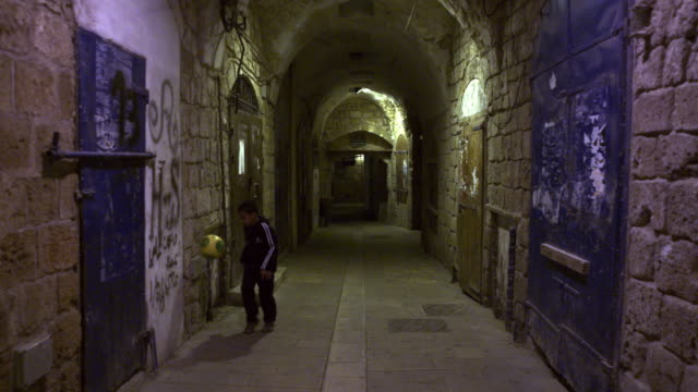 stock video footage of a boy juggling a soccer ball in an alley filmed in israel at 4k with red. - akko stock videos and b-roll footage
