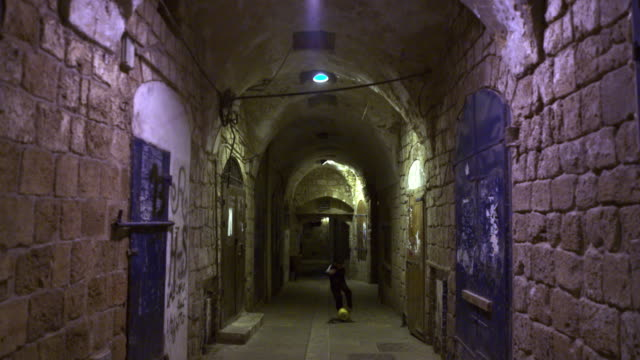 stock video footage of a boy playing soccer in an ancient alley filmed in israel at 4k with red. - akko stock videos and b-roll footage