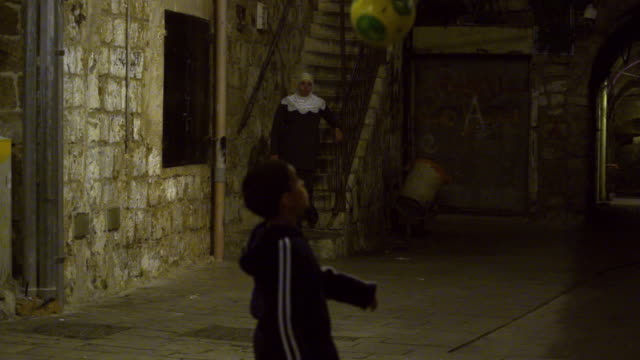 stock video footage of boy juggling a soccer ball at night filmed in israel at 4k with red. - akko stock videos and b-roll footage