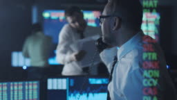 Stockbroker in white shirt is talking on the phone while working in a dark monitoring room with display screens.