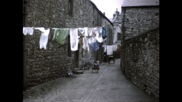 stone alleyway with clothesline hanging in the middle; little child in front of a door standing with a pot - 1950 stock videos & royalty-free footage