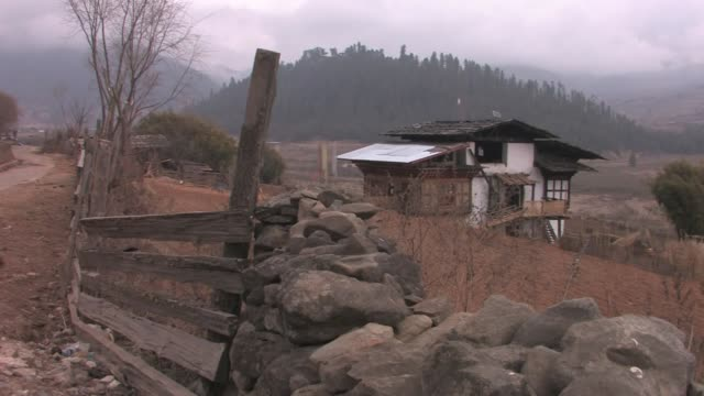 stone and wood fence in front of a house with prayer flags in the phobjikha valley. - stone house stock videos & royalty-free footage