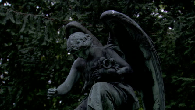 A stone angel kneels above a headstone in Lawnswood Cemetery, Leeds. Available in HD.