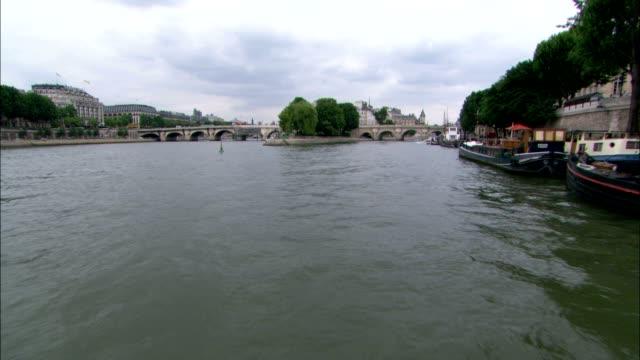 a stone arch bridge spans the river seine in paris. - arch bridge stock videos & royalty-free footage