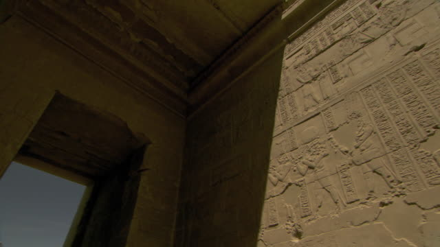 A stone archway at the Temple of Isis is decorated with hieroglyphs and carvings of deities and kings.
