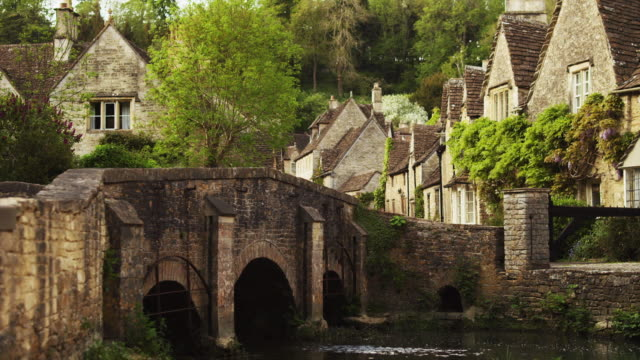 ws stone bridge in village / castle combe, cotswolds, wiltshire, uk - stone material stock videos & royalty-free footage