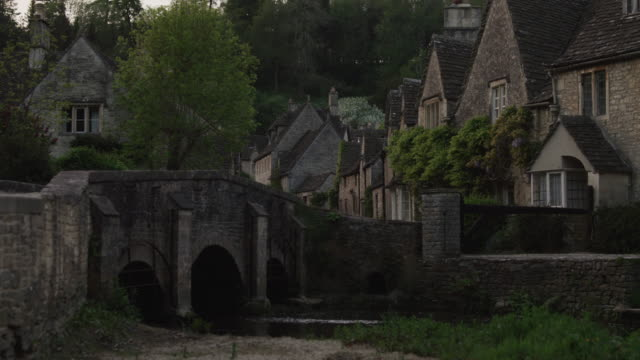 ws stone bridge in village / castle combe, cotswolds, wiltshire, uk - wiltshire stock videos & royalty-free footage