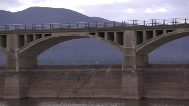 vídeos y material grabado en eventos de stock de a stone bridge spans a river  where light traffic passes. - acueducto