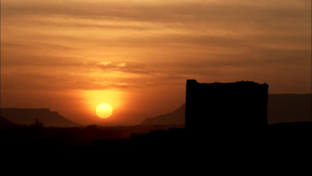 A stone building stands silhouetted against a pale orange sky and glowing yellow sun.