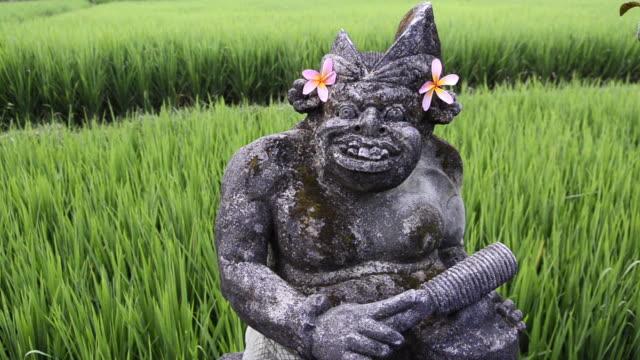 MS Stone carved god like figure with Frangipani flower in paddy field / Ubud, Bali, Indonesia