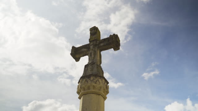 stone christian cross and blue sky in backlight - katholizismus stock-videos und b-roll-filmmaterial