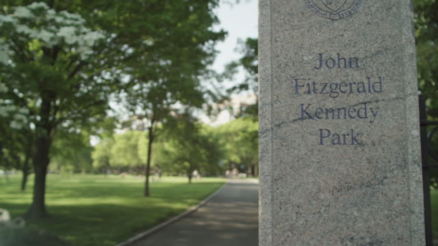 a stone column with the words john fitzgerald kennedy park stands in front of trees and a paved walkway. - ella fitzgerald stock videos & royalty-free footage