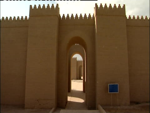 a stone corridor leads to an arched entryway. - babylon stock videos and b-roll footage