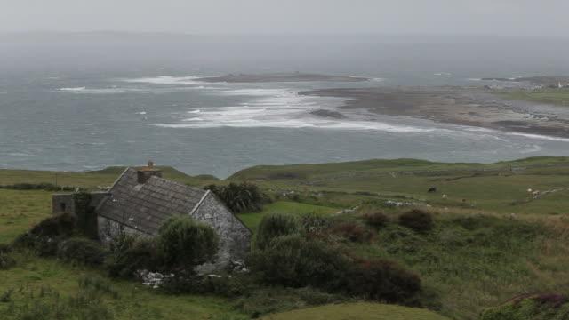 ws ha ld stone cottage on hillside near ocean / ireland - establishing shot stock videos & royalty-free footage