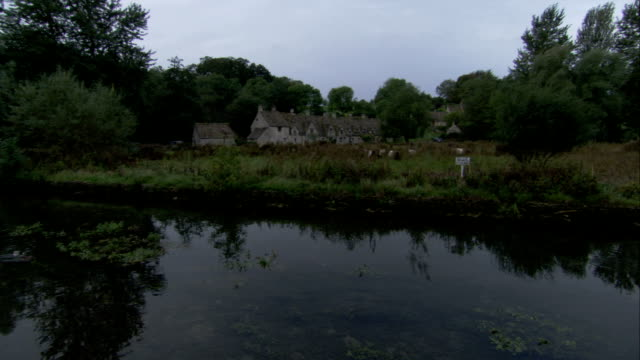 stone cottages line a calm, wooded river coln in bibury, gloucestershire, england. available in hd. - gloucestershire stock videos and b-roll footage