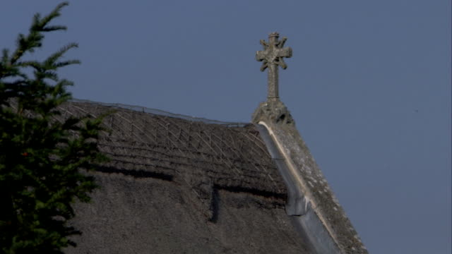 a stone cross decorates the eaves of an old english abbey. available in hd. - eaves stock videos and b-roll footage