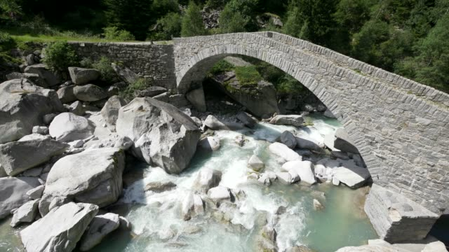 stone footbridge leading over wild mountain river in alpine environment - footbridge stock videos & royalty-free footage