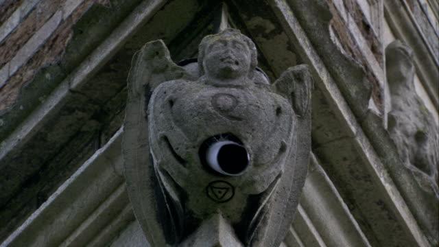 vídeos y material grabado en eventos de stock de a stone gargoyle perches on an upper corner of rushton triangular lodge in northamptonshire, england. available in hd. - northamptonshire