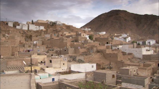 Stone houses crowd along a hillside in Djanet Algeria. Available in HD.