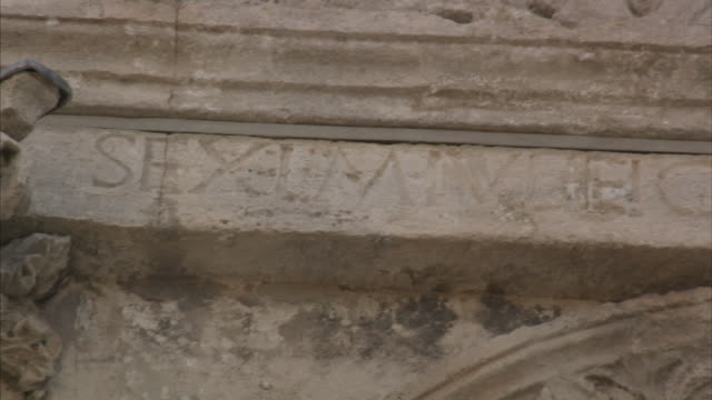A stone inscription shows evidence of weathering on Les Antiques of Glanum at Saint Remy de Provence in France.