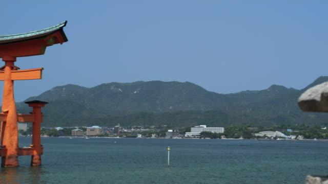 CU PAN WS Stone lantern and Torii gate at Itsukushima Shrine at high tide, Miyajima Island, Japan