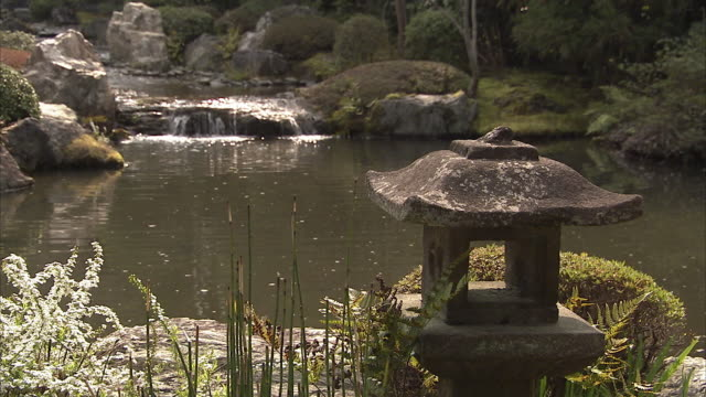 cu stone lantern in garden with pond in background, taizohin temple, kyoto, japan - ランタン点の映像素材/bロール