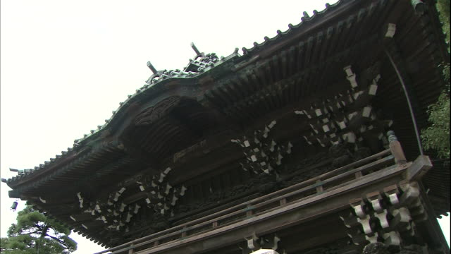a stone monument in front of a wooden gate identifies the shibamata taishakuten temple in tokyo, japan. - shibamata stock videos & royalty-free footage