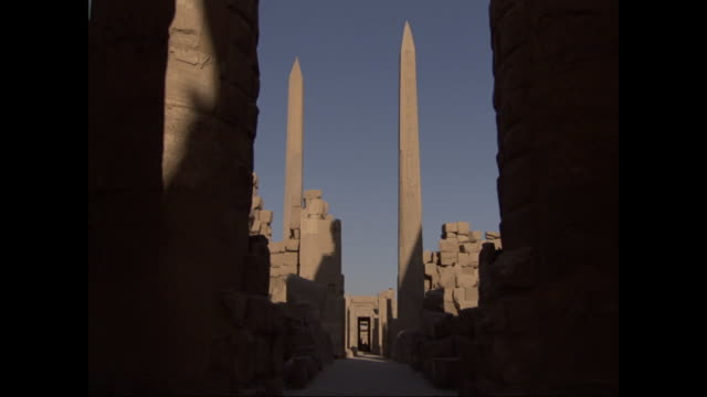 stone obelisks rise above ancient egyptian ruins. - obelisk stock-videos und b-roll-filmmaterial